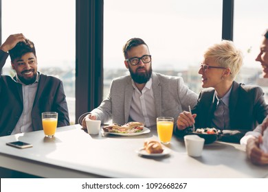 Group of business people having breakfast in company's restaurant. Focus on the man in the middle