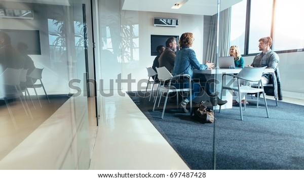 Gruppe von Geschäftsleuten, die im Konferenzraum diskutieren. Kreatives Geschäftsteam, das über neues Projekt nachdenkt.