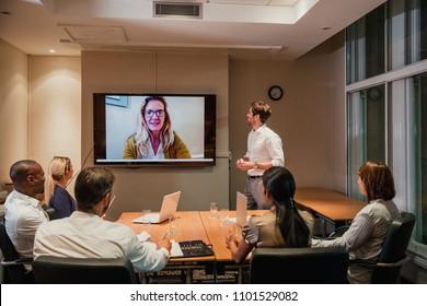 Gruppe von Geschäftsleuten, die eine Videokonferenz für die späte Nacht veranstalten. Sitzen um einen Konferenztisch Gespräch und Vernetzung.