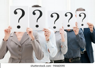 Group of business people hiding their faces behind a question mark sign at office