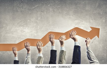 Group of business people holding growing graph in raised hands
