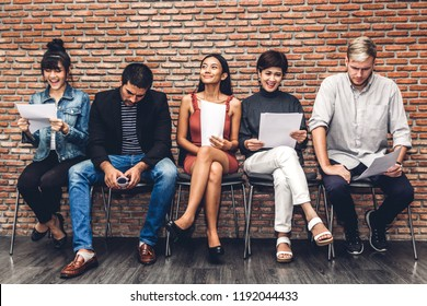 Group of business people holding paper while sitting on chair waiting for job interview against brick background