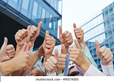 Group of business people holding their thumbs up next to the office outdoors