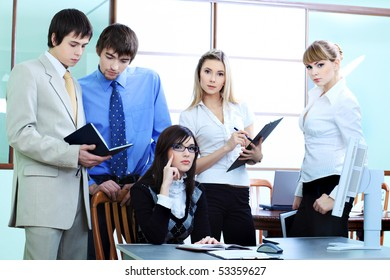 Group of business people interacting together at the office.