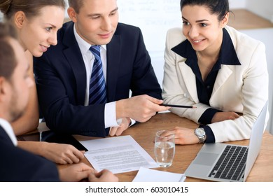 Group of business people and lawyers discussing contract papers sitting at the table. Focus at brunette woman looking at camera