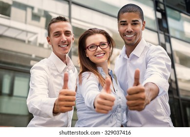 Group of business people looking at camera and showing thumbs up.