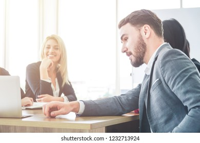 Group of business people looking at laptop screen during the meeting.