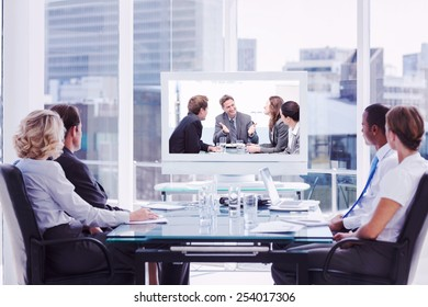 Group of business people looking at a screen against happy team laughing together at a meeting