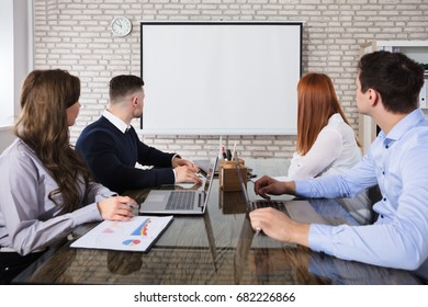 Group Of Business People Looking At White Board In Business Meeting