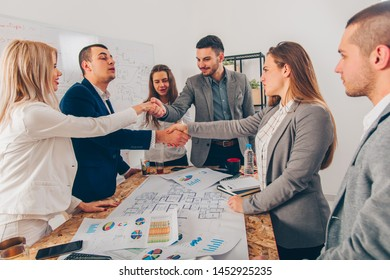 A group of business people are making a deal and shaking hands with the partners in the meeting room