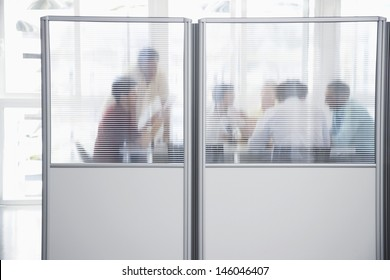 Group of business people in meeting behind translucent wall in office