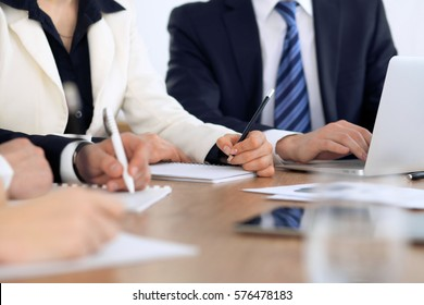Group of business people at meeting, close up of human hands in work with pen and papers