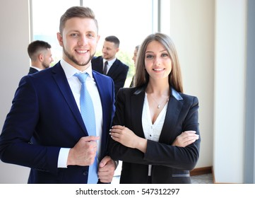 Group of business people at a meeting on the background of office. Focus on a beautiful brunet