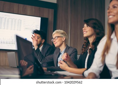 Group of business people on a meeting in a conference room. Woman raises hand to ask a question