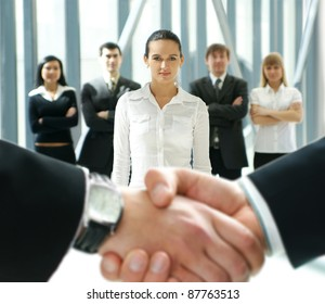 Group of business people over futuristic background with a blurry handshake in front