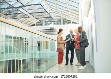 Group of business people planning their work day together while standing at corridor of business building