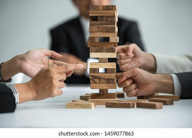 Group of business people playing game wooden blocks, business start up building, risk and growth.