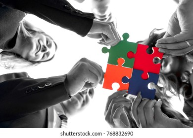 Group of business people puting togeher a puzzle. Strategy concept