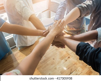 Group of business people putting their hands working together on wooden background in office. group support teamwork cooperation concept.