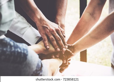 Group of business people putting their hands working together on wooden background in office. group support teamwork agreement concept.