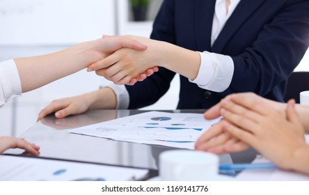 Group of business people shaking hands while finishing up a meeting. Handshaking, agreement or success concept in communication