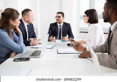 Group of business people sitting around the office desk and discussing the project together