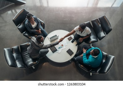 group of business people sitting and discussing statistics during a sit down meeting taking from above.