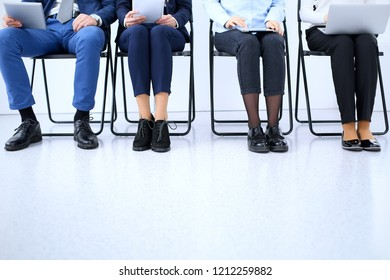 Group of business people sitting in office and waiting for job interview while using gadgets, close-up. Conference or training concepts