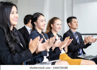 Group of business people sitting on conference together and smiling with clapping their hands at conference or other corporate event at meeting room.