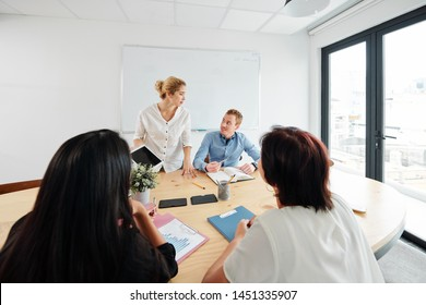 Group of business people sitting at the table and discussing working process in team during business meeting at board room