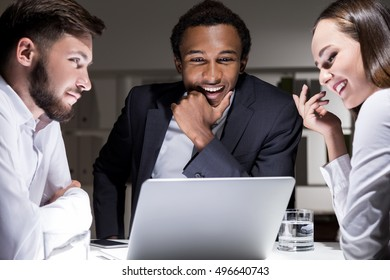 Group of business people are sitting at a table. They are admiring their African American boss and visioner skills. Concept of cult