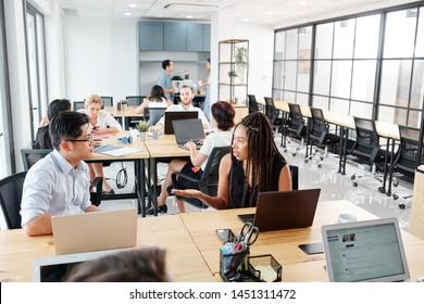 Gruppe von Geschäftsleuten, die am Arbeitsplatz mit Laptop-Computern arbeiten und Arbeitszeiten in modernen Büros diskutieren