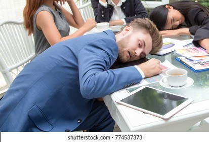Group of business people sleeping resting in the conference room , during work meeting, men and women relaxed sitting at office desk with closed eyes.