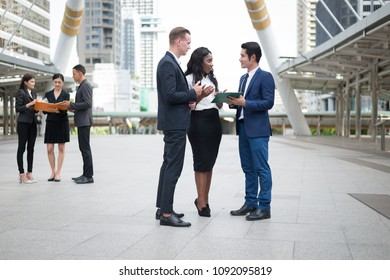 Group of business people standing in the city and discussing ideas for business future. multi culture of business people, African, Caucasian and Asian.