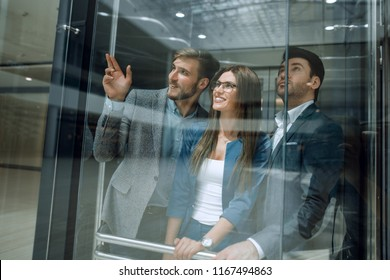 group of business people standing in glass Elevato
