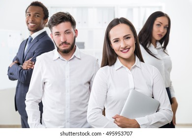 Group of business people standing together and smiling in office. Concept of collaboration.