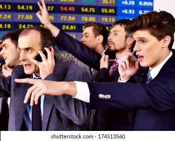 Group business people with  stock exchange board in office.
