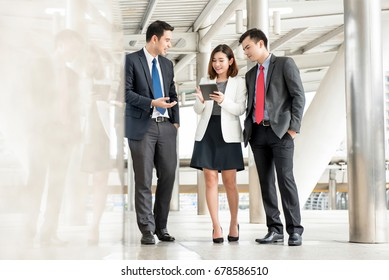 Group of business people talking and looking at tablet computer while walking in outdoor covered walkway