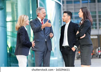 Group of business people talking outdoor in an urban setting
