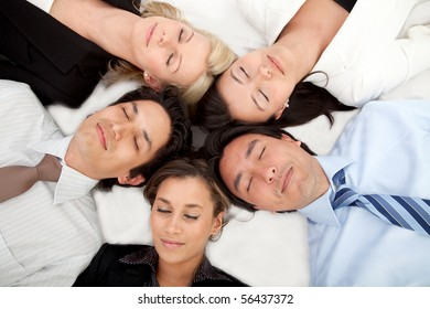Group of business people with their heads together on the floor and eyes closed