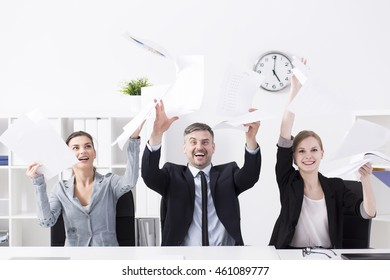Group of business people throwing documents in air