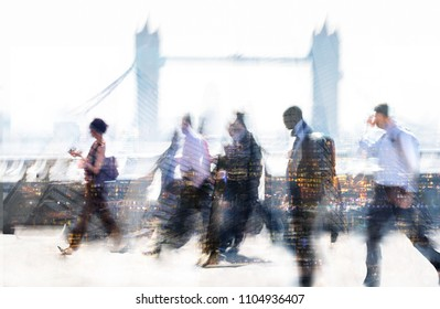 Group of business people walking over London bridge to the City of London. Early morning rush, modern life concept