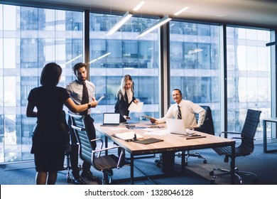 Group of business people working and communicating at late evening time in skyscraper office interior. Professional employees cooperating and discussing ideas during meeting. Team in entrepreneurship - Shutterstock ID 1328046128