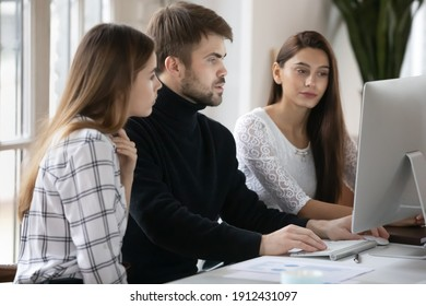 Group of business people working at computer together. Millennials team discussing project at workplace. Mentor training interns, showing learning video to new employees. Internship, teamwork concept