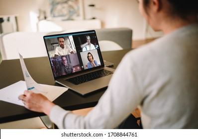 Group of business people working from home, having video conference. Businesswoman having a video call with her team over a laptop at home.
