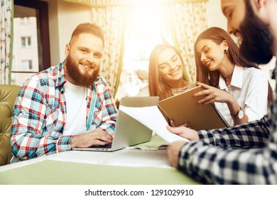 Group of business people working on laptop in cafe. Smiling mans holding documents. Happy smiling people working online while using notebook. Freelance work, business people concept.
