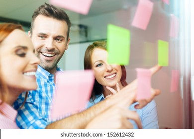 Group of business people working on new project with many sticky notes on window