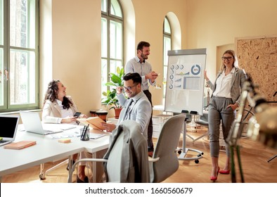 Group of business people working together in office, two coworker conducting a business presentation using flip chart.