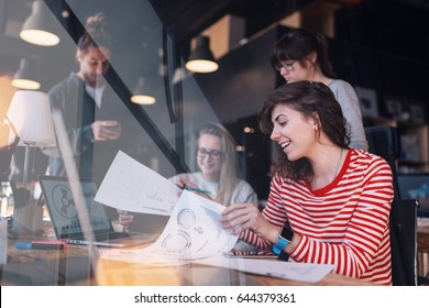 Group of business people working together in big coworking office. PR department discussing new product stats. Intentional lens flares and window reflection