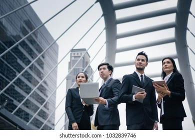 Group of business peoples standing outdoors with office building in the background, look to target at the sky